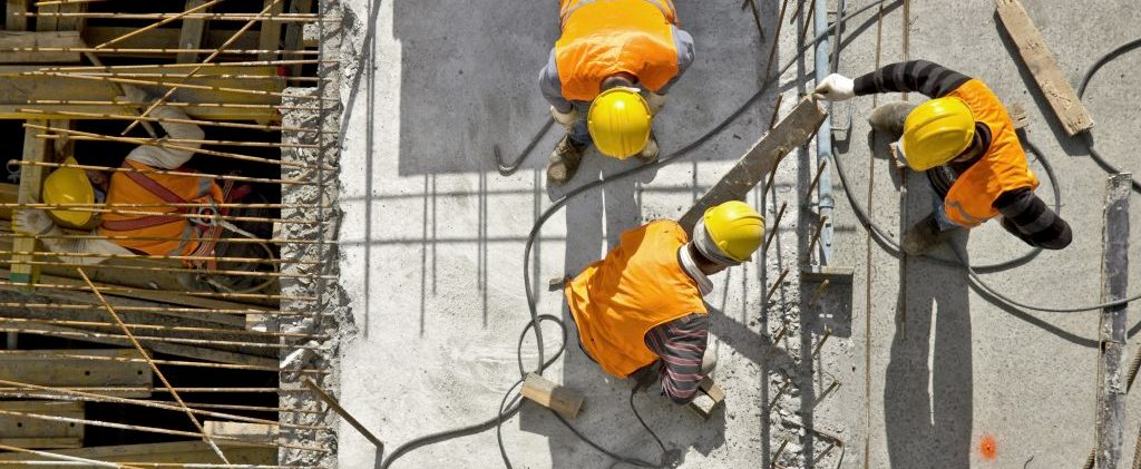 construction workers standing and working with rebar mesh for concrete walls and floors