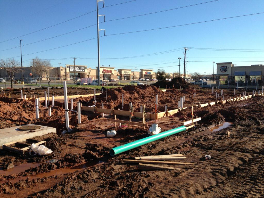 a foundation of a new construction project with plumbing hook ups and lots of dug up mud everywhere