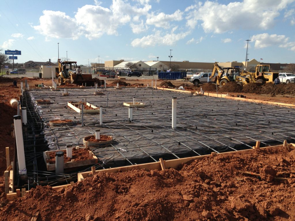 a foundation of a new construction project with rebar mesh and plumbing hook ups