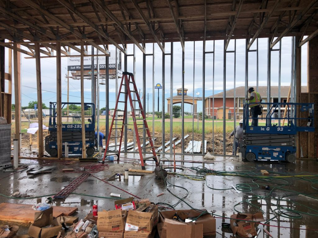 construction workers inside of a steel-framed building with supplies everywhere